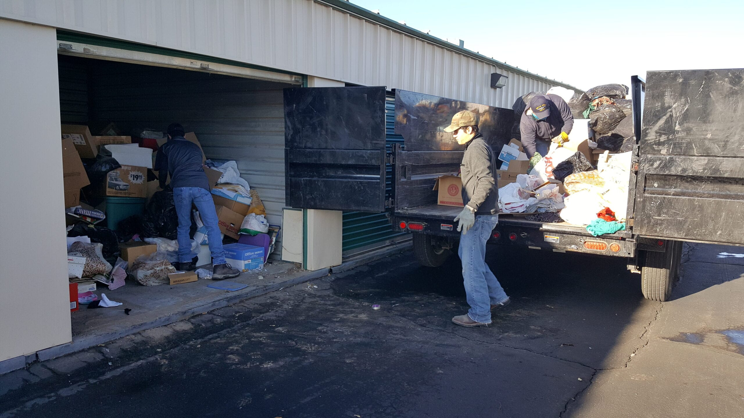 Employees clearing out a storage unit with hoarded excess garbage